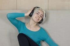 Mujer joven rubia feliz que se sienta en el sofá con listeni de los auriculares Imagen de archivo libre de regalías
