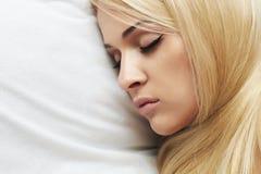 Mujer joven rubia hermosa que duerme en el bed.girl fotografía de archivo