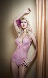 Mujer joven rubia hermosa y atractiva que lleva el corsé rosado que presenta provocativo contra la pared cerca de las cortinas. Pe Foto de archivo