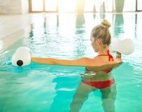 Mujer joven rubia que hace aeróbicos de la aguamarina Imagen de archivo