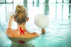 Mujer joven rubia que hace aeróbicos de la aguamarina con pesas de gimnasia en la natación Imagen de archivo libre de regalías