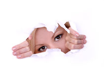 Mujer joven rubia que mira furtivamente a través del agujero en el papel imagenes de archivo