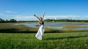 Mujer joven rubia que se coloca al revés sonriente en un paisaje hermoso del campo al aire libre con los brazos de manos del aume fotografía de archivo