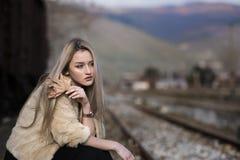 Mujer joven rubia que se sienta en la plataforma del ferrocarril del borde Foto de archivo