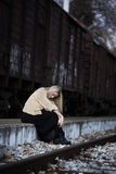 Mujer joven rubia que se sienta en la plataforma del ferrocarril del borde Fotos de archivo