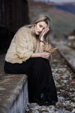 Mujer joven rubia que se sienta en la plataforma del ferrocarril del borde Fotos de archivo libres de regalías
