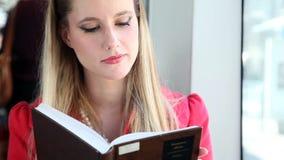 Mujer joven rubia que se sienta en la tranvía, libro de lectura metrajes