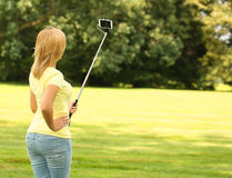 Mujer joven rubia que toma la foto del selfie con el palillo en parque Imágenes de archivo libres de regalías