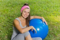 Mujer joven sana de la aptitud con la bola de Pilates al aire libre Foto de archivo libre de regalías