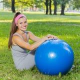 Mujer joven sana de la aptitud con la bola de Pilates al aire libre Fotos de archivo libres de regalías