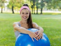 Mujer joven sana de la aptitud con la bola de Pilates al aire libre Imagenes de archivo