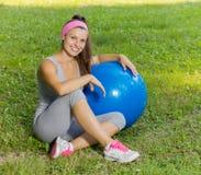 Mujer joven sana de la aptitud con la bola de Pilates al aire libre Fotografía de archivo