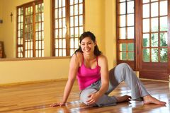 Mujer joven sana en el equipo de la gimnasia que se sienta en el suelo fotos de archivo