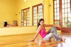 Mujer joven sana en el equipo de la gimnasia que se sienta en el suelo foto de archivo