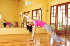 Mujer joven sana en estirar del equipo de la gimnasia imagen de archivo