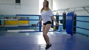 Mujer joven sana en los pantalones cortos que saltan con la cuerda que salta en gimnasio en el ring de boxeo metrajes