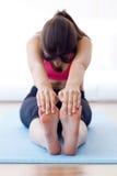 Mujer joven sana hermosa que hace ejercicio en casa Imagenes de archivo