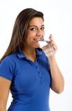 Mujer joven sana que bebe un vidrio de agua Foto de archivo libre de regalías