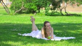 Mujer joven sana que come la manzana verde y la sonrisa almacen de video