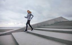 Mujer joven sana que corre abajo en pasos Foto de archivo