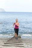 Mujer joven sana que corre en la playa del thr Imágenes de archivo libres de regalías