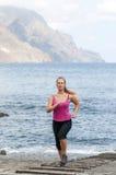 Mujer joven sana que corre en la playa del thr Fotos de archivo libres de regalías