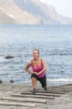 Mujer joven sana que corre en la playa del thr Imagen de archivo libre de regalías