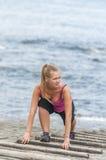 Mujer joven sana que corre en la playa del thr Fotografía de archivo