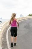Mujer joven sana que corre en la playa del thr Imagenes de archivo