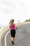 Mujer joven sana que corre en la playa del thr Foto de archivo