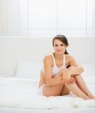 Mujer joven sana que se sienta en cama Imagenes de archivo