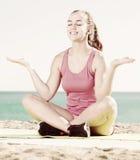 Mujer joven satisfecha que ejercita en la estera del ejercicio al aire libre fotos de archivo