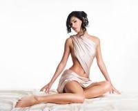 Mujer joven sensual con el cuerpo hermoso en la seda beige Imagenes de archivo