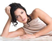 Mujer joven sensual con el cuerpo hermoso en la seda beige Fotos de archivo libres de regalías