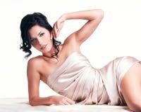 Mujer joven sensual con el cuerpo hermoso en la seda beige Foto de archivo libre de regalías