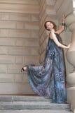 Mujer joven sensual encantadora en vestido muy largo diáfano en las escaleras Fotos de archivo libres de regalías