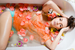 Muchacha bastante atractiva que toma un baño con los pétalos de la flor imagen de archivo