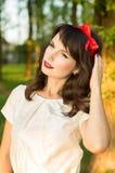 Mujer joven sensual, presentando dulce en el jardín Imagenes de archivo