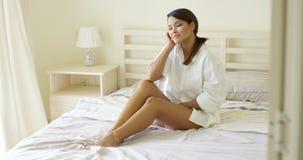 Mujer joven sensual que estira en su cama almacen de metraje de vídeo
