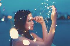 Mujer joven sensual que juega con las luces de hadas al aire libre que miran a Imágenes de archivo libres de regalías