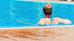 Mujer joven sensual que se relaja en piscina almacen de metraje de vídeo