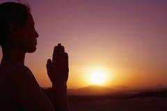 Mujer joven serena con las manos junto en actitud del rezo en el desierto en China, silueta, ajuste del sol, perfil Fotografía de archivo