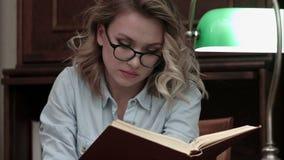 Mujer joven seria en los vidrios que buscan el informaton en el libro almacen de video