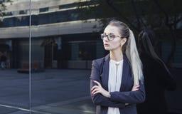 Mujer joven seria en traje y vidrios Imagenes de archivo