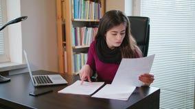 Mujer joven seria que mira en documentos almacen de metraje de vídeo