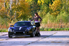 Mujer joven sexual que se coloca cerca del coche deportivo inferior Foto de archivo libre de regalías