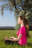 Mujer joven siiting en la hierba en actitud de la yoga Imagenes de archivo