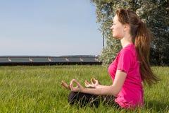 Mujer joven siiting en la hierba en actitud de la yoga Imágenes de archivo libres de regalías