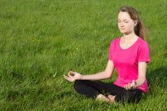 Mujer joven siiting en la hierba en actitud de la yoga Fotos de archivo