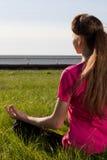 Mujer joven siiting en la hierba en actitud de la yoga Fotografía de archivo